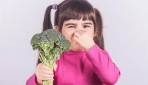 Little girl refusing to eat her vegetables